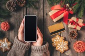 cropped view of woman holding smartphone with blank screen on wooden background with credit card and christmas gifts