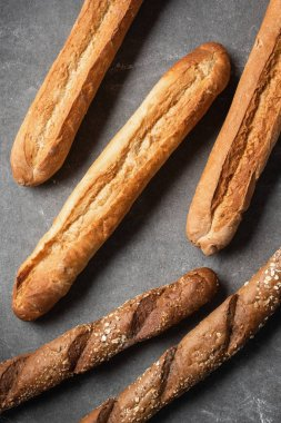 Full frame of arranged loafs of baguettes on grey tabletop stock vector