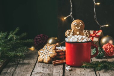 gingerbread man in cup of cocoa with marshmallows on wooden table with christmas light garland