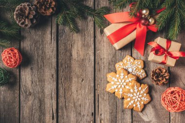 top view of gingerbread snowflakes and christmas gifts on wooden background with copy space