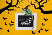 Photo beautiful exotic chameleon on blackboard with a wee bit wicked lettering and bats isolated on yellow