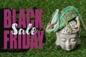 Fotografie beautiful bright green chameleon sitting on Buddha head with black friday sale