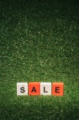 Fotografie red and wooden alphabet cubes with sale sign on green grass