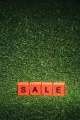 Fotografie red alphabet blocks with sale sign for black friday on green grass