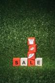 červené a dřevěná abeceda kostky s prodej znamení a oblečení na zelené trávě na černý pátek