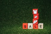 Fotografie red and wooden alphabet cubes with sale sign and clothes on green grass