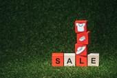červené a dřevěná abeceda kostky s prodej znamení a oblečení na zelené trávě
