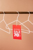 Fotografie hangers with red super sale tag - 70 percents discount on beige