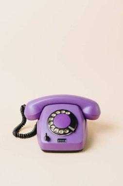 one purple vintage telephone on beige