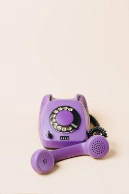purple vintage rotary telephone with tube on beige