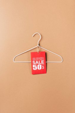 Hanger with red super sale tag with fifty percents discount on beige stock vector