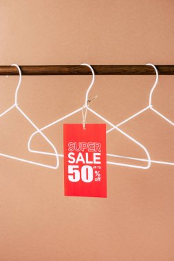 Hangers with red super sale tag - 50 percents discount for black friday shopping on beige stock vector