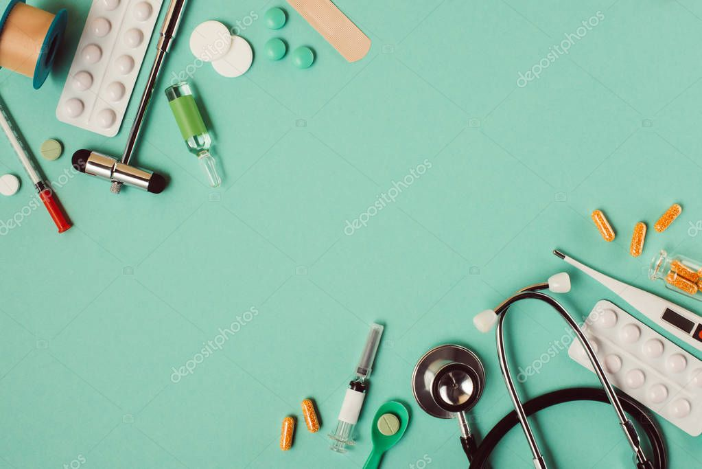 Top view of various medical pills and instruments on green background stock vector