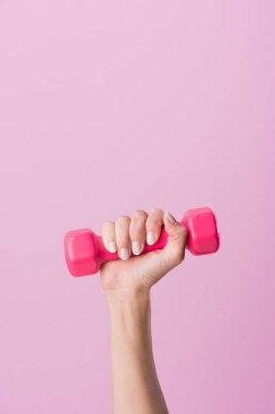cropped shot of woman holding dumbbell isolated on pink