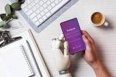 částečný pohled podnikatel kyborg rukou pomocí smartphone s Instagramem na obrazovce u stolu s šálkem kávy v kanceláři