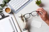 Oříznout obrázek podnikatel kyborg rukou drží brýle u stolu s prázdnou návštěva karet a klávesnice počítače v kanceláři
