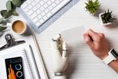 oříznutého obrazu podnikatel kyborg rukou a smartwatch drží Prázdná vizitka u stolu s smartphone s infografika na obrazovce v úřadu