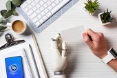 körülvágott kép üzletember cyborg kezét és smartwatch gazdaság üres névjegykártyát a smartphone-val shazam képernyőn az office-tábla