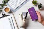 Oříznout obrázek podnikatel protézy rukou drží kreditní kartu a pomocí smartphone s Instagramem na obrazovce u stolu v kanceláři