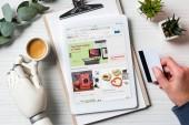 Oříznout obrázek podnikatel kyborg rukou drží kreditní kartu a pomocí digitálních tabletu s ebay na obrazovce u stolu s šálkem kávy v kanceláři