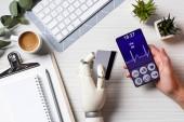 částečný pohled podnikatel kyborg rukou drží kreditní kartu a pomocí smartphone s lékařských aplikací na obrazovce u stolu s šálkem kávy v kanceláři