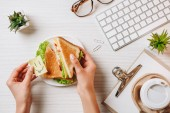 Fotografie partial view of businesswoman holding symbol of smile having lunch with sandwich and coffee in paper cup at table in office