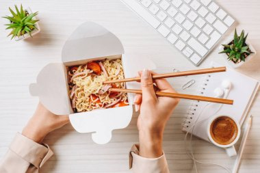 cropped image of businesswoman eating noodle by chopsticks at table with coffee cup and computer keyboard in office