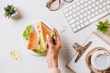 cropped image of businesswoman having lunch with sandwich and coffee in paper cup at table with symbol of smile in office