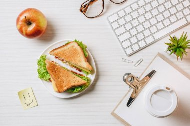 top view of workplace with sandwich, paper coffee cup, apple and symbol of smile at table in office