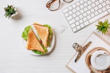 view from above of disposable coffee cup, sandwich, computer keyboard and eyeglasses at table in office