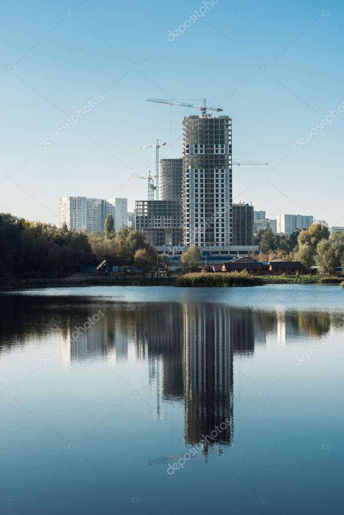 modern buildings with reflection in lake in city in autumn