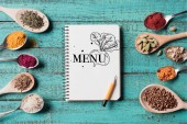 Fotografie top view of menu inscription in notebook with pencil and spoons with various spices on turquoise wooden surface