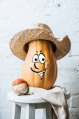 Photo close up view of ripe pumpkins with drawn smiley facial expression and straw hat on wooden surface and white brick wall backdrop
