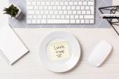 Fotografie pohled shora poznámky s nápisem čas na oběd na talíř, počítačové myši a klávesnice na pracovišti