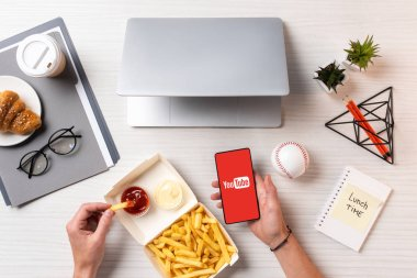 cropped shot of person eating french fries with ketchup and using smartphone with youtube app at workplace