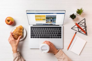 Cropped shot of businesswoman holding disposable coffee cup and croissant while using laptop with booking website stock vector