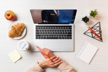 cropped shot of female hands, laptop with booking website and lunch on table in office