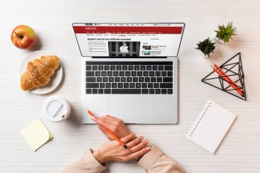 Cropped shot of female hands, laptop with bbc news and lunch on table in office stock vector