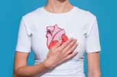 cropped shot of woman in white tshirt with paper made heart on blue backdrop