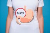 oříznutý snímek ženy s papírem vyrobeno žaludku a rakoviny písmem na modrém podkladu