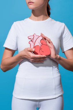 cropped shot of woman in white tshirt holding paper made heart on blue backdrop