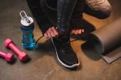 Fotografie Oříznutý pohled ženy utahovací tkaničky na její tenisky