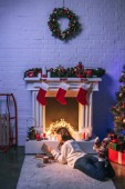 Rozkošná žena čte poblíž vánoční zdobené krb a vánoční stromeček