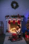 atraktivní žena pomocí smartphone poblíž vánoční zdobené krb a vánoční stromeček