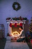 krásná žena, sedí poblíž zdobený krb a vánoční stromeček