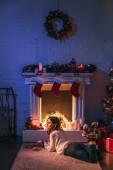 atraktivní žena ležící poblíž vánoční zdobené krb a vánoční stromeček