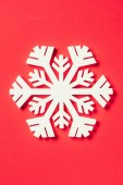 Fotografie top view of paper snowflake on red background