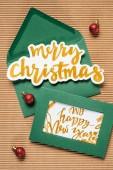 flache Lage aus grünen Umschlägen mit frohen Weihnachten und frohem neuen Jahr Zeichen auf dem strukturierten Hintergrund