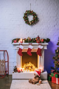 Fireplace with Christmas decorations near Christmas tree with gifts