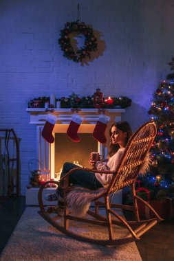beautiful woman sitting in the rocking chair near fireplace and Christmas tree